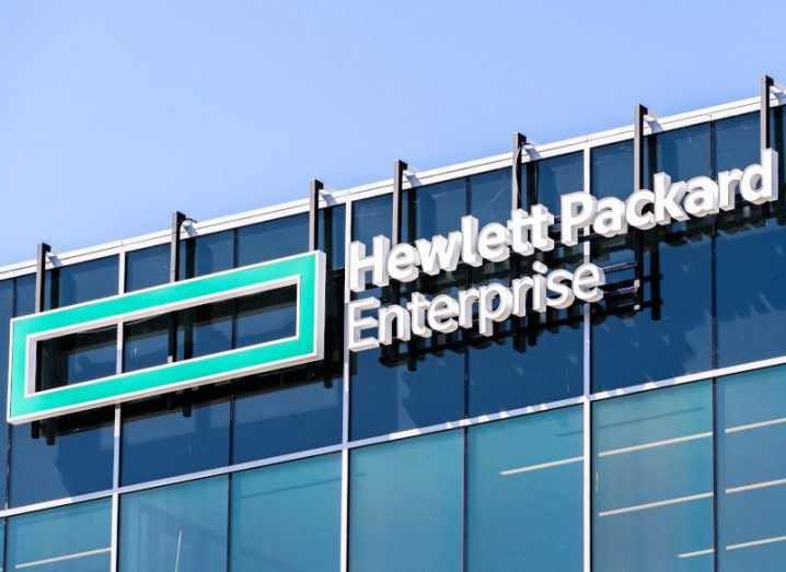 Hewlett Packard Enterprise logo on the side of a building against a blue sky.