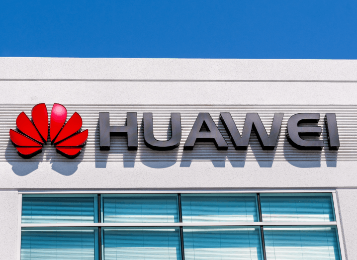 The Huawei logo on the front of a white building underneath a blue sky.