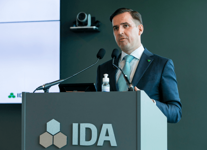A man with black hair wearing a navy suit and green tie stands at a podium with the IDA logo on it.
