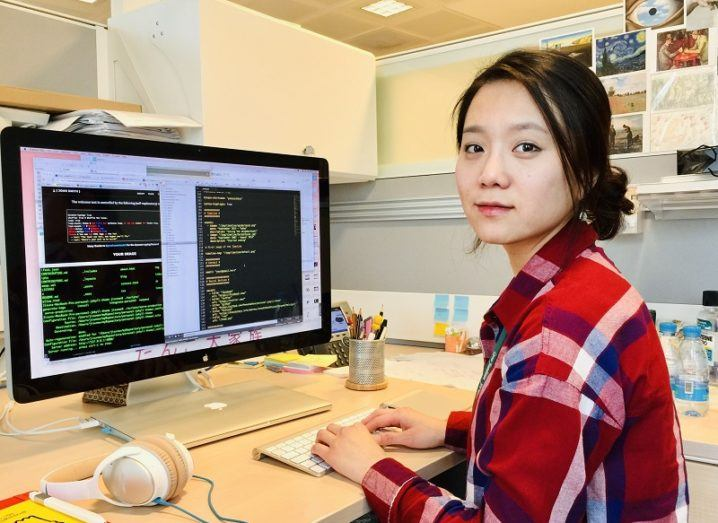 Jisun An in a tartan shirt turned to the camera while working at a desktop screen in her lab.