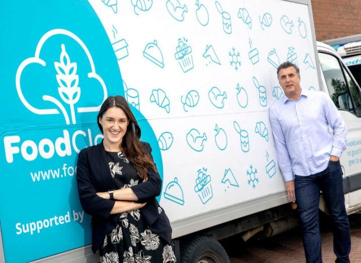 A woman and a man stand a few metres apart in front of a white and blue van with the FoodCloud logo on the side.