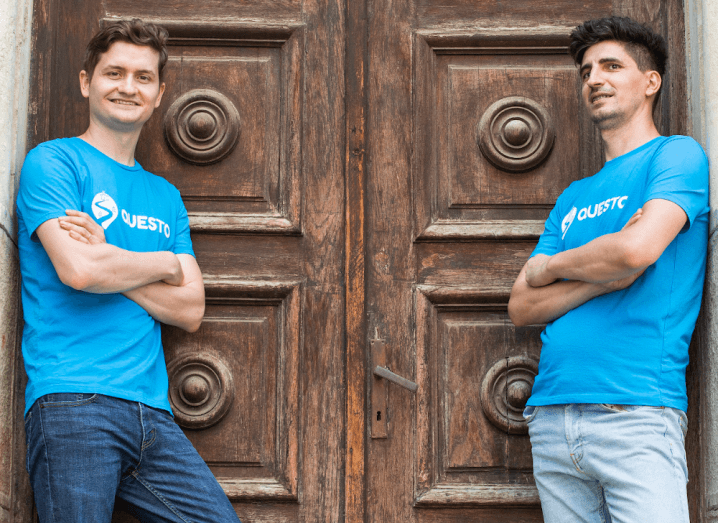 Two men in blue t-shirts stand at a wooden door with their arms crossed.