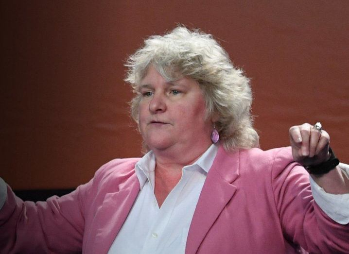 Rebecca Parsons wearing a white shirt and a pink blazer while speaking at an event, with her arms outstretched.