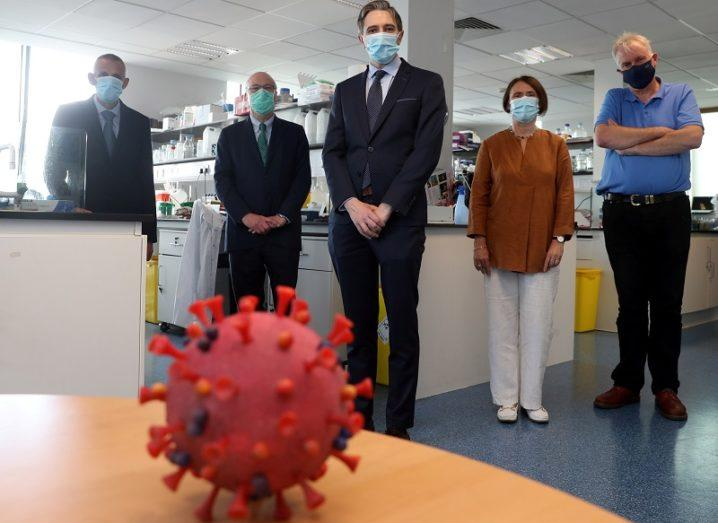 Kingston Mills, Mark Ferguson, Simon Harris, Aideen Long and Luke O'Neill wearing face masks and standing behind a model of the coronavirus.