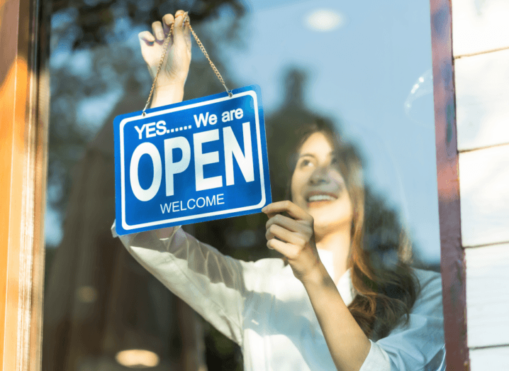 A woman wearing a white blouse puts a blue sign in a shop window. The sign says open.