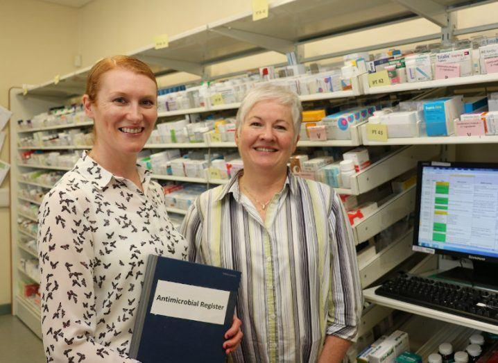 Two women stand in a pharmacy storeroom with fully stocked shelves of treatments. They are standing in front of a desktop computer and one woman holds a folder that reads 'antimicrobial register'.