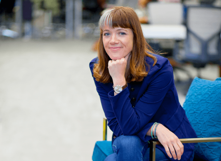 A woman with brown hair with a grey streak in her fringe sits with her fist raised to her chin on a blue chair. She is wearing a blue blazer and blue jeans.
