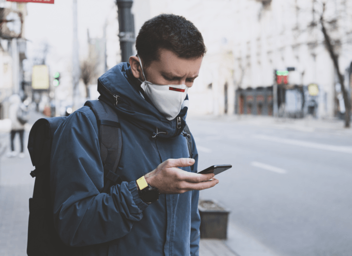 A young man wearing a white mask with a blue jacket stands on a street looking at his phone. He has brown hair and is also wearing a black backpack.