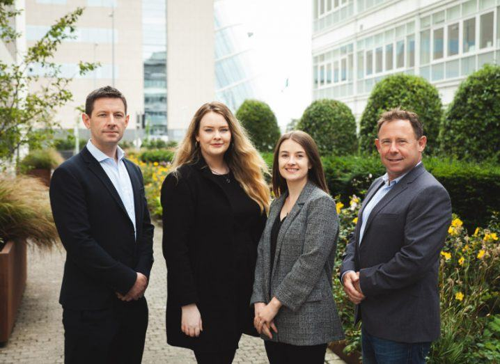 Four team members from Circit are standing in professional clothing in a modern outdoor business campus, smiling into the camera.