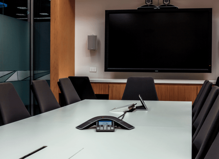 A conference room with a television mounted on the wall and a phone in the centre of a table, surrounded by seven chairs.