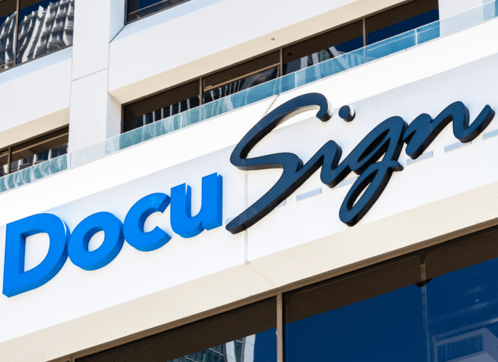 The DocuSign logo on the front of a building. There are windows above and below the logo, which is printed in blue and navy.