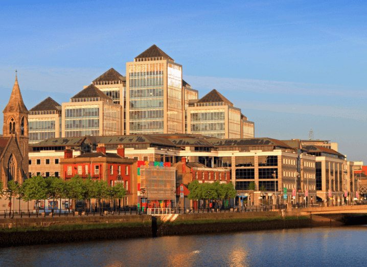 Tall buildings along the quays of the Liffey river in Dublin. There is a mix of modern office blocks and older churches and commercial buildings.