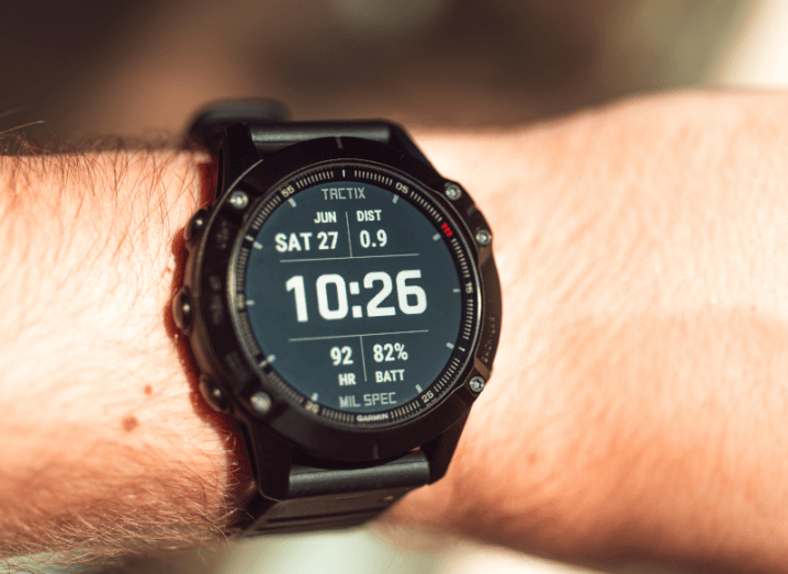 A large, black smartwatch on a person's arm.