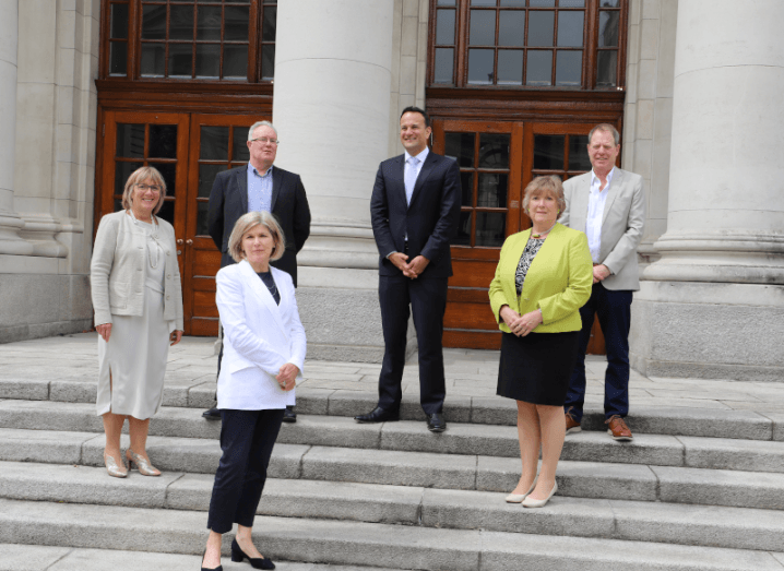 Three men and three women standing on the steps of the Dáil at a distance from each other.
