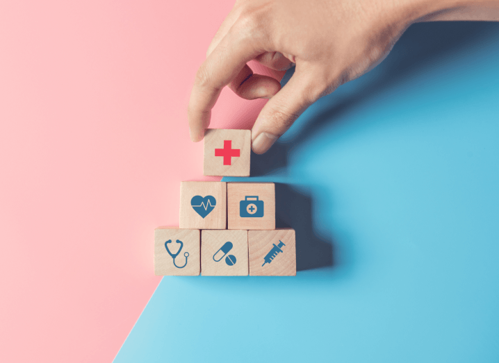 A person piling up blocks with healthcare symbols on them.