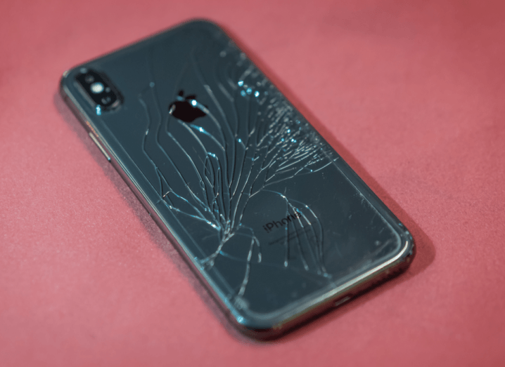 A smashed smartphone on a pink background.