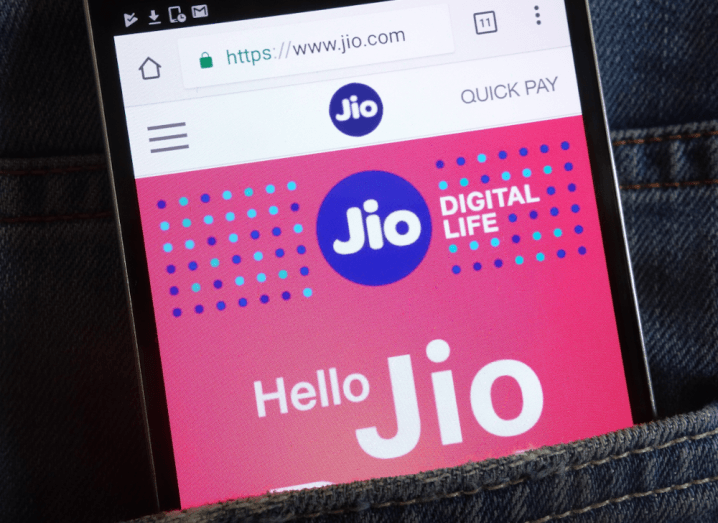 The Reliance Jio Platforms logo on a smartphone screen in the back pocket of a pair of denim jeans.