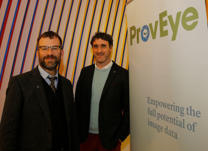 Two men in casual suits standing against a sign that says ProvEye.