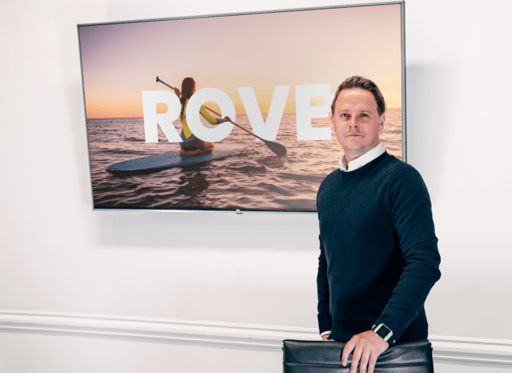 A man in a navy jumper and white shirt standing in front of a TV screen with the Rove logo displayed on it.