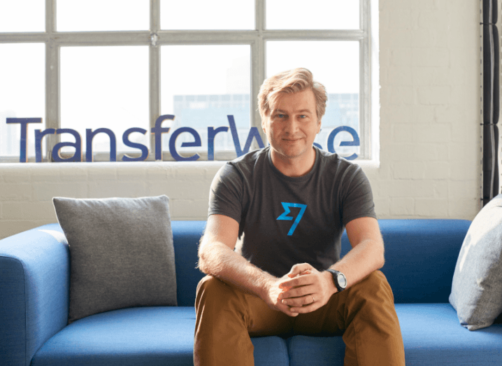 A man with blonde hair sits on a blue sofa wearing a grey T-shirt and chinos. The T-shirt has the TransferWise logo on it. Behind the sofa there is a window and another TransferWise logo.
