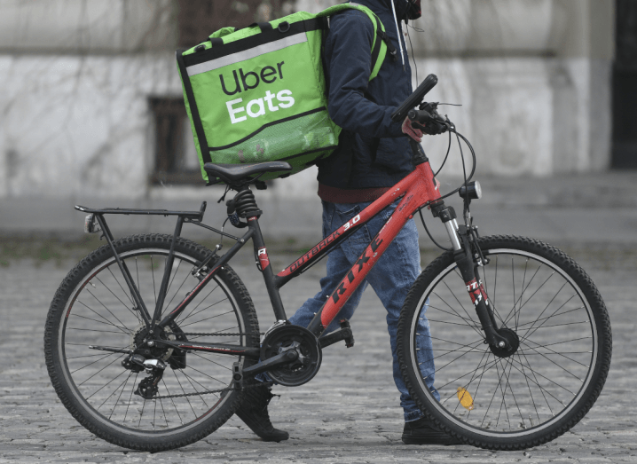 A person wearing a navy jacket and blue jeans pushes a red bike along a city street. They have a large green Uber Eats bag on their back.