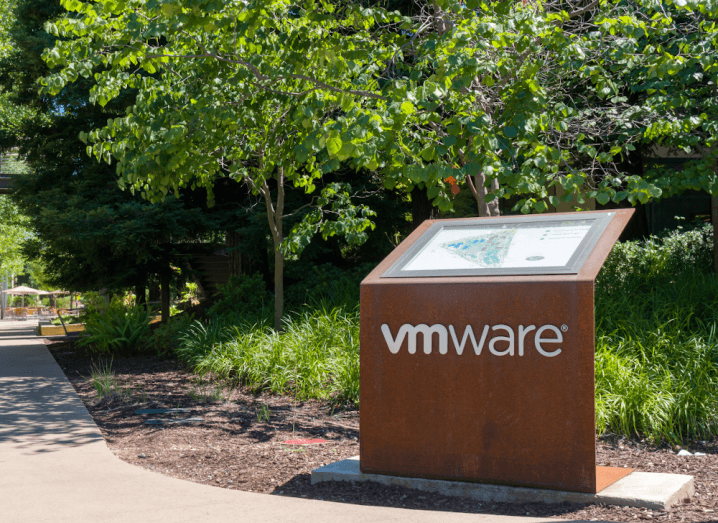 The VMware logo on a sign in front of trees.