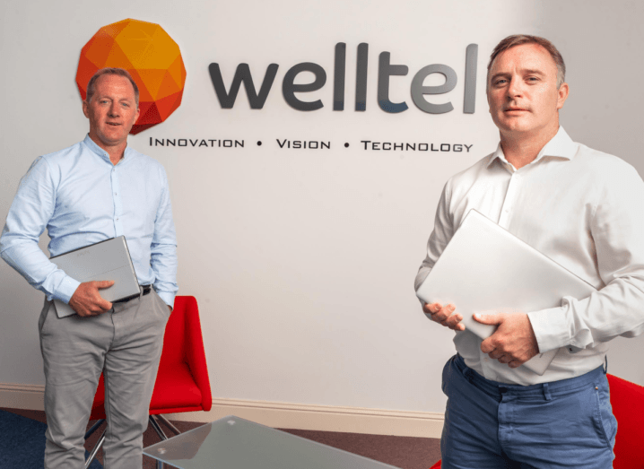 Two men stand in front of a wall with the Welltel logo on it. The man on the left wears a blue shirt and grey slacks, while the man on the right wears a white shirt and blue chinos. They both have light brown hair.