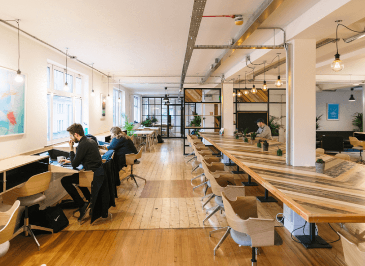 A bright office space with people working at a physical distance.