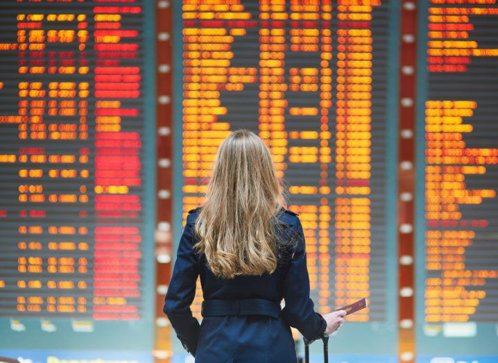 A woman travelling with her passport and cabin baggage on-hand looks at a large screen of flight information in an airport.