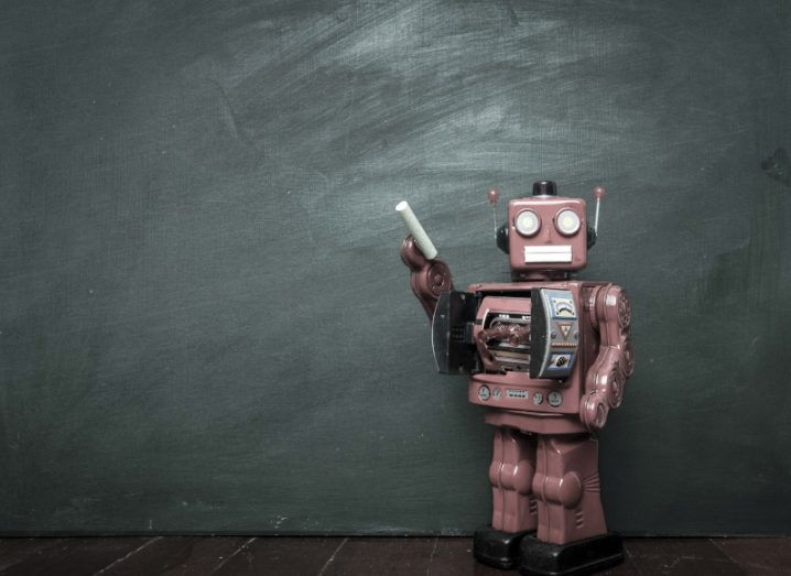 A toy robot holds a piece of chalk next to a blackboard, symbolising the algorithm's involvement in dictating Leaving Cert results.