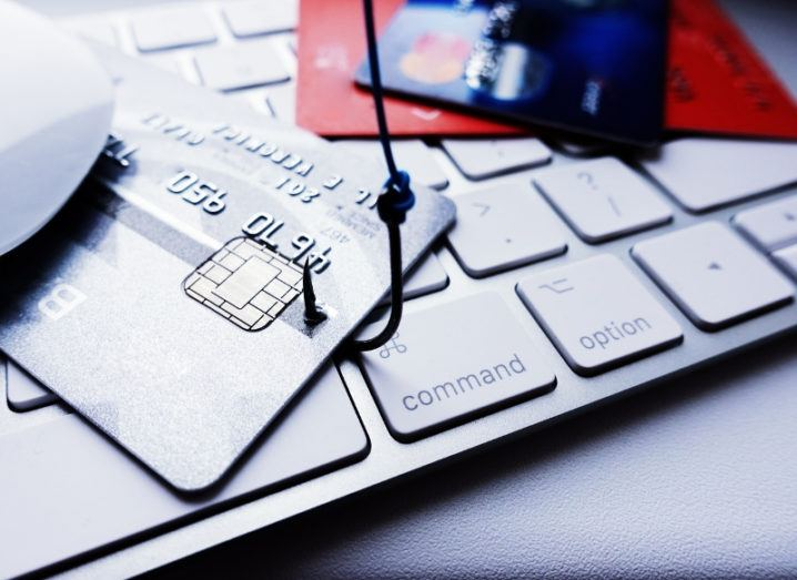 A fishing hook is piercing a credit card on a computer keyboard.