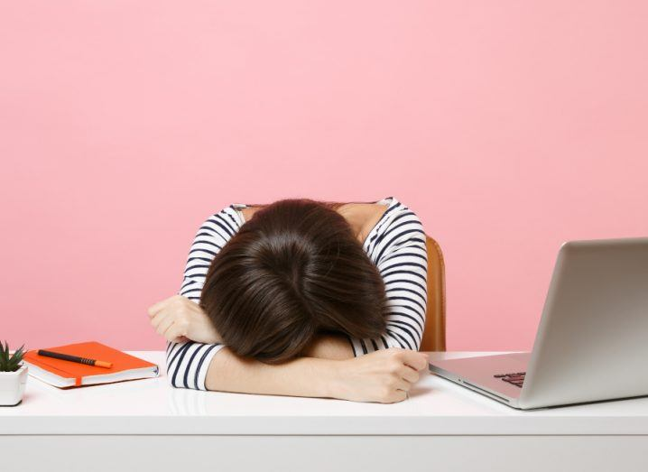 A young woman with dark hair is laying her head on a desk beside her laptop. She is sitting in a bright pink office space.