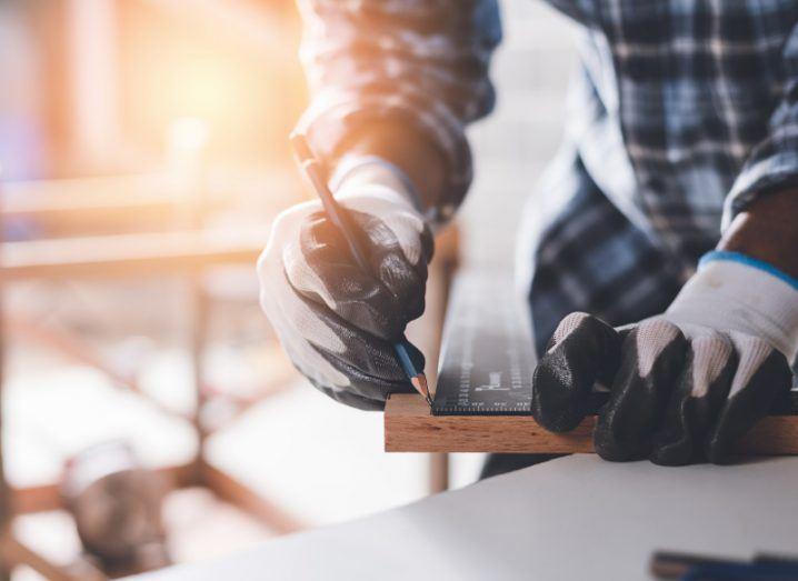 A carpenter cutting a piece of wood in a woodwork workshop.