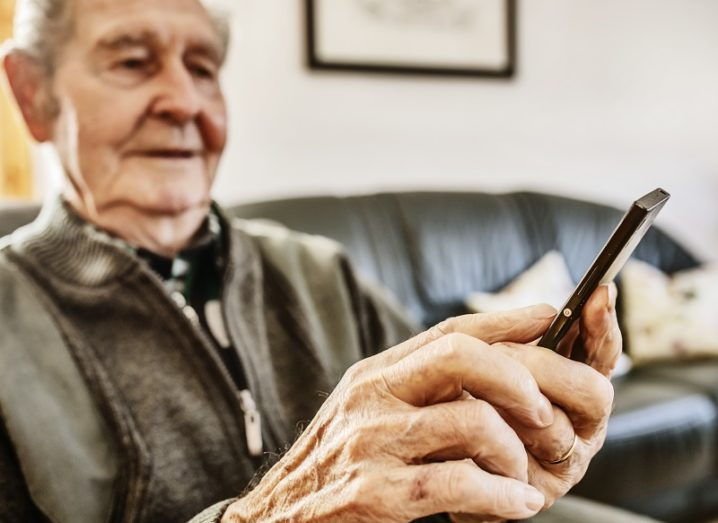 Old man looking at a mobile phone in a sitting room with a couch.