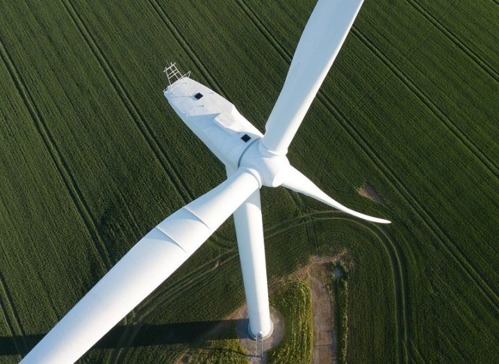 Close-up aerial shot of a wind turbine in a field.