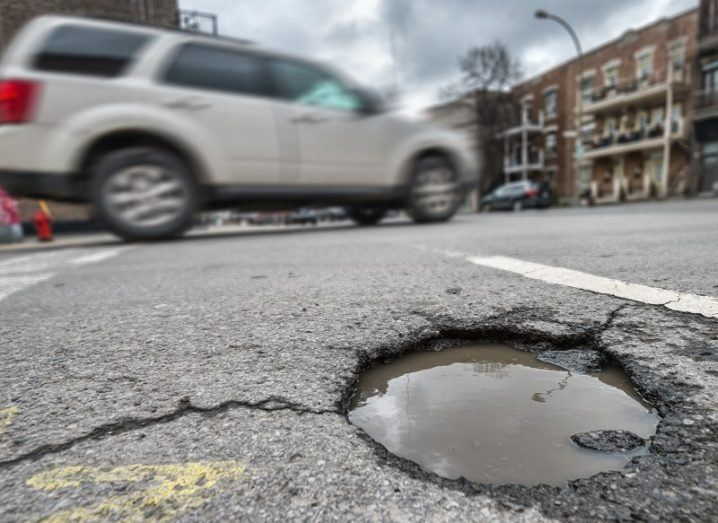 Close-up of a large pothole in a road, with a car driving past on a city street.