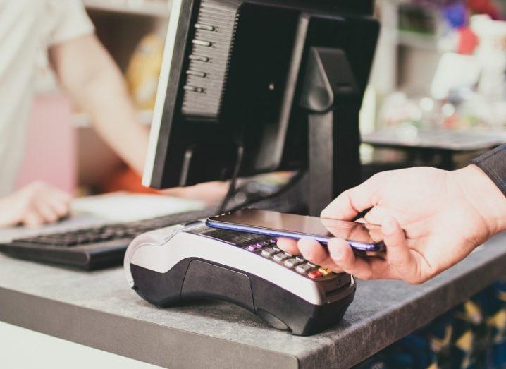 Person paying at a terminal with their smartphone.