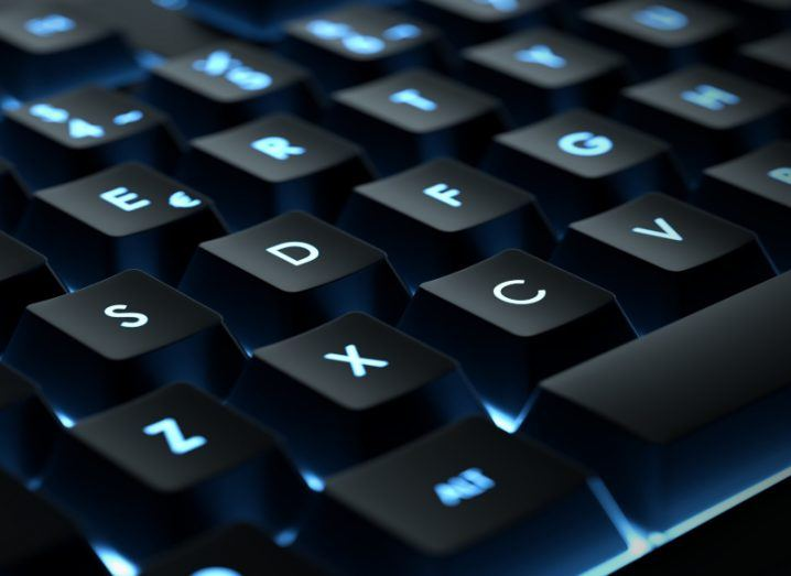 A close-up of a computer keyboard, with bright blue backlighting.