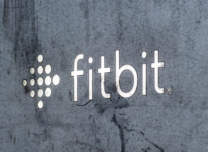 The Fitbit logo emblazoned on a grey stone wall.