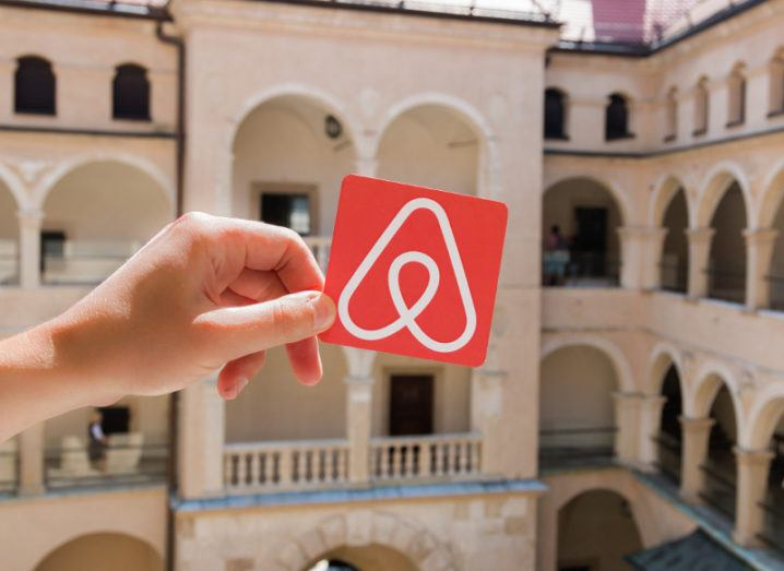 A hand is holding the Airbnb logo up to the camera in front of accommodation in Minsk.