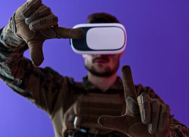 Man in soldier outfit and wearing a VR headset holding his hands up against a purple background.