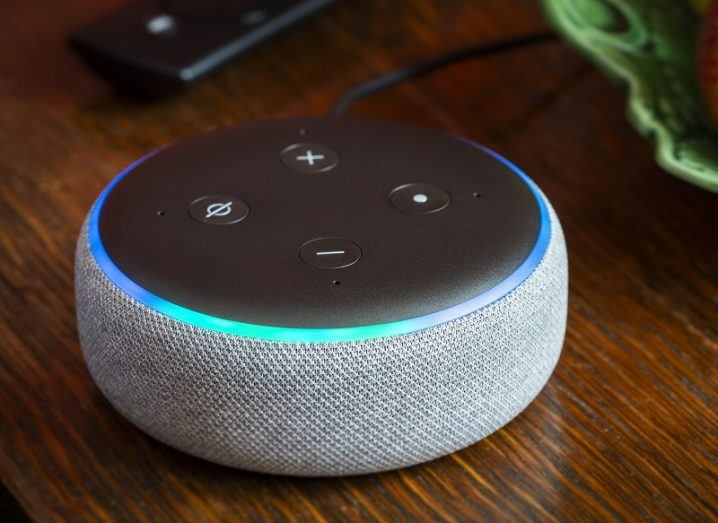 An Amazon Echo Dot on a wooden table.