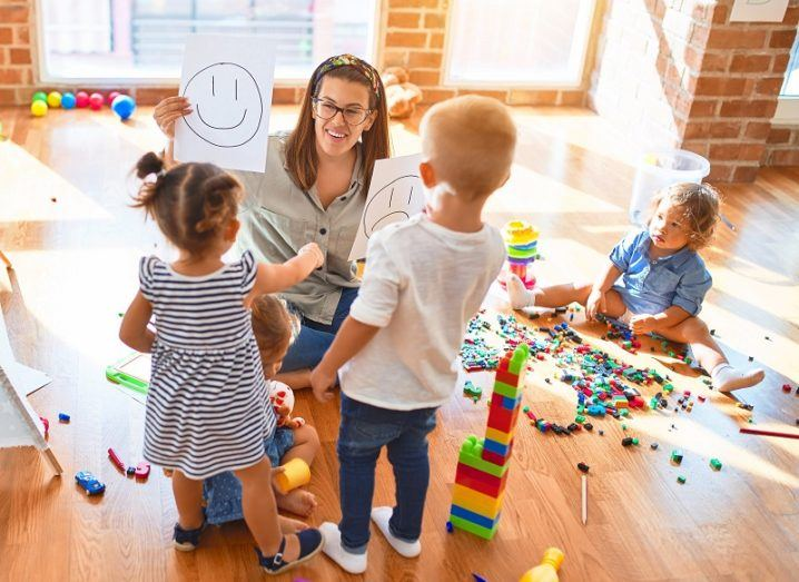 Teacher playing with three young children in a brightly lit classroom surrounded by toys.