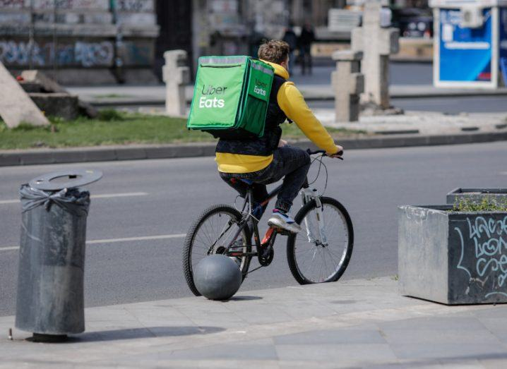 A person wearing an Uber Eats backpack cycles a bike through an empty city street.