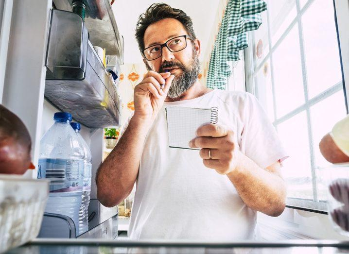 A man stands next to his open fridge door with a notepad in hand, ready to make a meal plan.