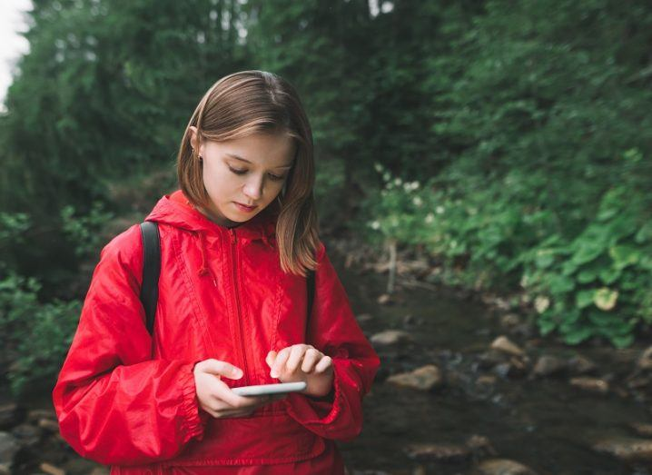 Woman in a red raincoat looking at her phone beside a river and trees.