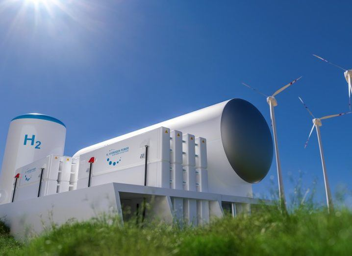 Concept of a hydrogen fuel tank beside a wind farm on a sunny day.