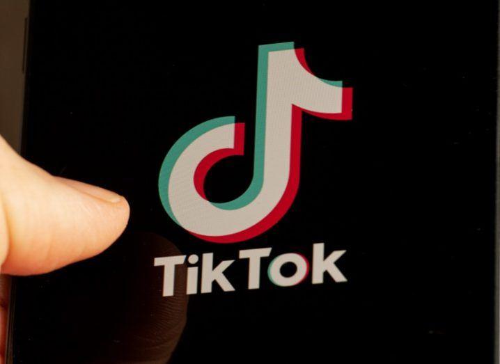 Thumb beside a screen showing the TikTok logo.