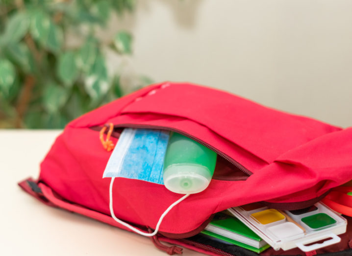 A red schoolbag lies open on a table and inside you can see a bottle of green hand sanitiser, a blue face mask, some books and a set of paints.
