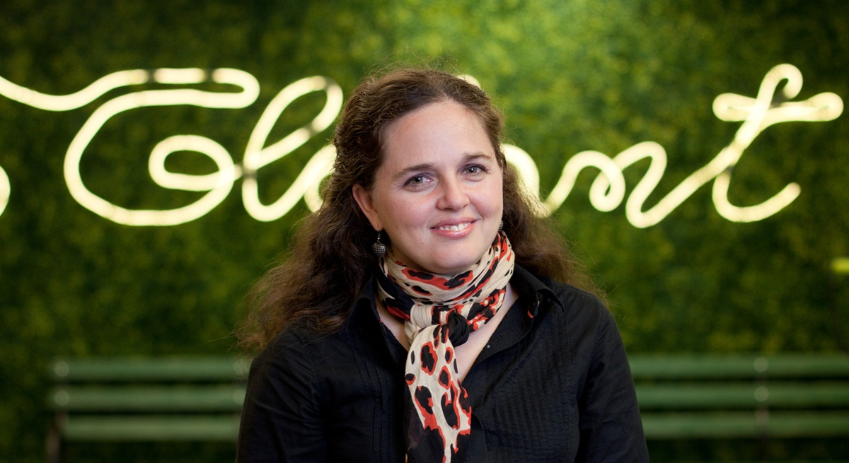 Mercedes MacPherson of Globant is sitting in front of a green neon sign for the company and smiling into the camera.